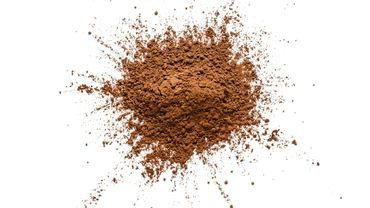 Cocoa powder heap shot from above on white bachground