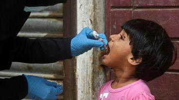 Un membre d'une équipe de vaccination administre des gouttes de vaccin contre la polio à un enfant à Karachi
