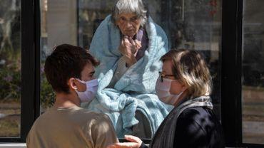 La brésilienne Eunice Schleier (R) et son fils Alexandre parlent respectivement à leur mère et à leur grand-mère, Olivia Schleier (C), 81 ans, à travers une fenêtre de l'hôpital Premier, à Sao Paulo, Brésil, le 28 mai 2020. l'hôpital n'a aucun cas de COVID-19 mais ne permet pas de visites pour prévenir les contagions du nouveau coronavirus.