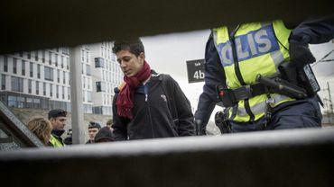 Un migrant est escorté par un policier suédois, dans une gare de Malmö, le 12 novembre 2015