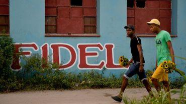 Des Cubains marchent face au nom Fidel inscrit sur un mur, à La Havane le 21 novembre 2019