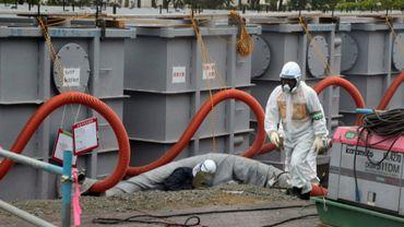Les travailleurs de TEPCO sur les conteneurs d'eau toxique à Fukushima