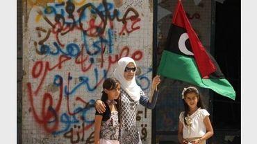 Une femme, accompagnée de ses filles, agite le drapeau des rebelles libyens du CNT près du bunker de Mouammar Kadhafi, le 31 août 2011.