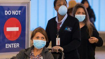 Des passagers portant des masques de protection contre le coronavirus débarquent à l'aéroport de Los Angeles le 5 mars 2020.