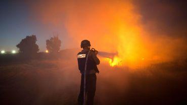 Un pompier israélien éteint un incendie provoqué par une roquette de Gaza