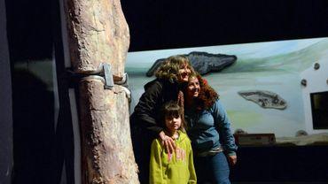 Des visiteurs posent à côté du fémur de ce qui pourrait avoir été le plus grand dinosaure au monde, au Musée paléontologique Edigio Peruglio de Trelew, en Argentine