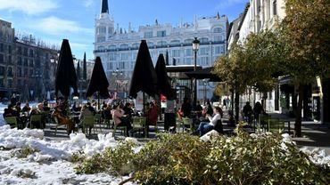 Assis à une terrasse à Madrid le 14 janvier 2021 près d'arbres tombés pendant une tempête de neige historique