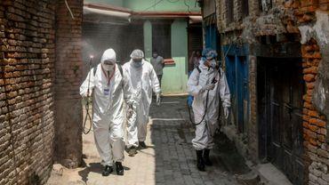Des employés en combinaison de protection désinfectent les ruelles d'un quartier de Katmandou, le 3 mai 2020 au Népal
