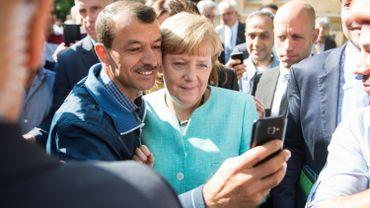 Un demandeur d'asile prend un selfie avec la chancelière allemande, Angela Merkel,  à la suite de sa visite dans une succursale de l'Office fédéral des migrations et des réfugiés et dans un camp de demandeurs d'asile à Berlin le 10 septembre 2015