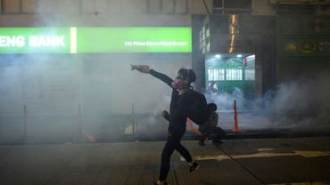 Un manifestant hongkongais renvoie une cartouche de gaz lacrymogène tirée par la police lors d'échauffourées le 7 octobre 2019 dans le district de Mongkok