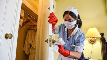 Une employée de l'Hotel Nacional de Cuba nettoie et désinfecte une chambre après le passage de touristes, le 14 mars 2020 à La Havane