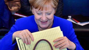 La chancelière allemande Angela Merkel sort un dossier de son sac avant une réunion du groupe parlementaire CDU/CSU à Berlin, le 2 juillet 2018