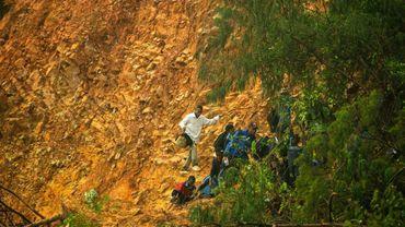 Des écoliers et des membres du personnel de l'école Saint Charles Luanga marchent sur le site d'un glissement de terrain à Chimanimani, au Zimbabwe; le 17 mars 2019