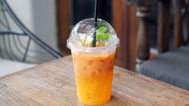 Iced tea with lemon and orange in plastic glass on wooden table.