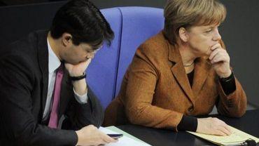 Le ministre de l'Economie Philipp Rösler(g) etla chancelière Angela Merkel lors d'une séance au parlement allemand, le 15 décembre 2011.