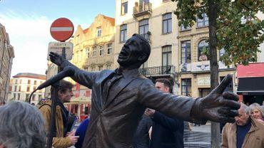"""La sculpture intitulée """"L'envol"""" est en bronze. Elle représente l'artiste derrière son micro, les bras ouverts. Elle est orientée en direction de la rue du Chêne."""