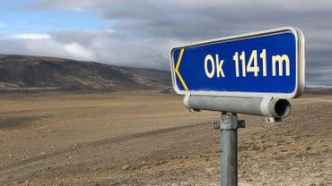"""Sur le bord de la route, un petit panneau avec des lettres et nombres jaunes sur fond bleu indique: """"Ok 1.141 m"""" et pointe en direction du glacier disparu et de son sommet."""
