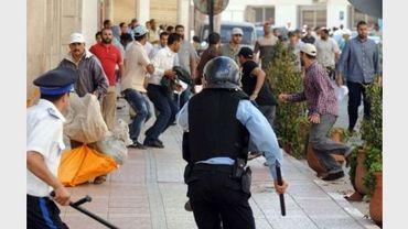 Un policiers poursuit des manifestants, le 22 mai 2011 à Rabat