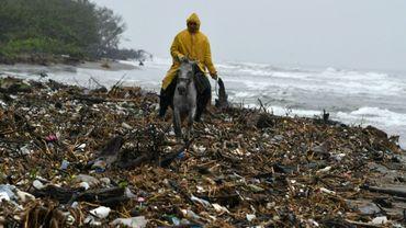 Un homme à cheval au milieu des ordures sur la plage d'Omoa, une ville côtière au nord du Honduras, le 11 novembre 2017