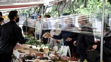 Un film plastique entre des clients et des vendeurs de fruits et légumes sur un marché à Paris en mai 2020.