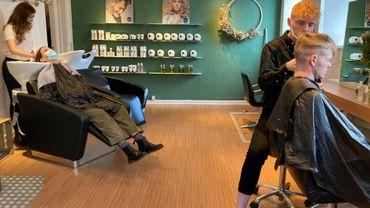 Des clients dans un salon de coiffure du centre de Copenhague, le 6 avril 202. Le Danemark a commencé à exiger que les gens utilisent une nouvelle application Covid pour pouvoir accéder à certains commerces sous peine d'amende, une première en Europe.