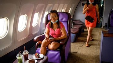 Dans la ville touristique de Pattaya, ces passagers d'un nouveau type prennent place dans les sièges de la premier classe d'un avion désaffecté.