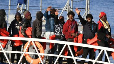 Migrants wave while disembarking from one of Malta's AFM Protector-class coastal patrol boats on January 9