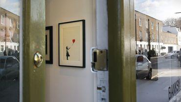 """La toile est une reproduction en peinture acrylique et aérosol de l'une des plus célèbres images de Banksy, """"Girl with Balloon"""", montrant une petite fille laissant s'envoler un ballon rouge en forme de coeur."""
