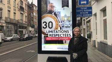 Catherine Morenville, échevine Ecolo de l'urbanisme, et un des panneaux publicitaires contestés.