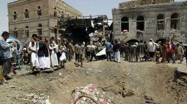 Des personnes devant un cratère probablement creusé par une bombe d'un raid aérien de la coalition arabe sous commandement saoudien à Sanaa au Yémen, le 19 septembre 2015