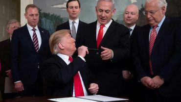 Donald Trump tend son stylo au Premier ministre israélien Benjamin Netanyahu après avoir signé le décret reconnaissant officiellement la souveraineté d'Israël sur le plateau du Golan, le 25 mars 2019 à Washington