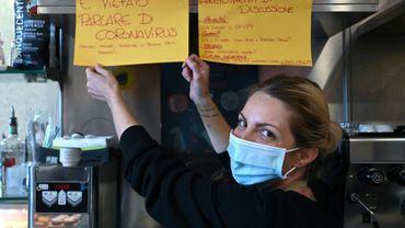 """Cristina Mattioli  pose devant un panneau disant """"il est interdit de parler du coronavirus"""" dans son bar """"Feeling"""" près de Rome le 19 novembre 2020"""