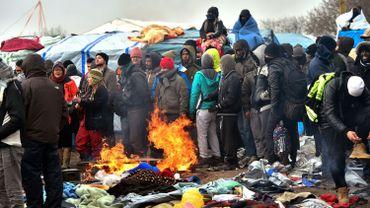 """Des migrants tentent de se réchauffer pendant qu'une partie de la """"Jungle"""" est démantelée"""