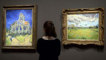"""Une visiteuse contemple """"L'Eglise d'Auvers-sur-Oise vue du chevet"""" et """"Paysage sous un ciel tourmenté"""", des oeuvres de Vincent Van Gogh exposées au Musée d'Orsay dans le cadre de """"Van Gogh/Artaud"""""""