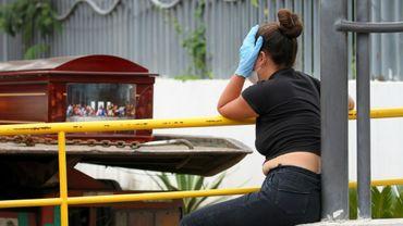 Une femme, portant un masque et des gants de protection, pleure près d'un cercueil à l'extérieur d'un hôpital de Guayaquil, le 1er avril 2020 en Equateur