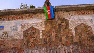 Haut-Karabakh: un soldat azerbaÏdjanais accroche son drapeau à Jabrayil repris par les forces de Bakou le 16 octobre