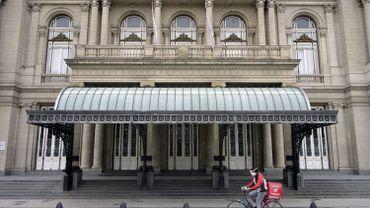 Cycliste avec un masque de protection devant le théâtre Colon, fermé, à Buenos Aires, fin avril 2020