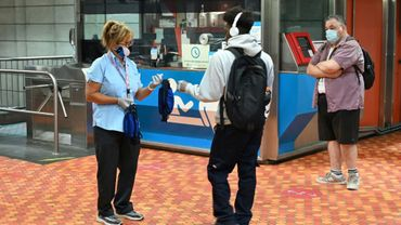 Une employée du métro de Montréal distribue des masques aux voyageurs n'en portant pas.