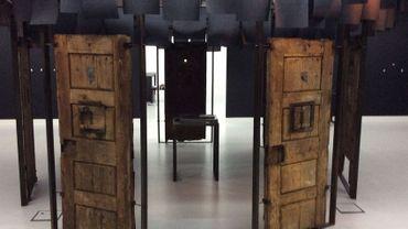 7 portes authentiques datant de l'incarcération de Paul Verlaine exposées en cercle au BAM