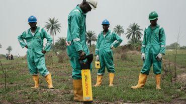 Des travailleurs équipés de détecteurs dans le cadre du nettoyage de la pollution pétrolière le 19 février 2019 à Eleme, dans le sud du Nigeria.
