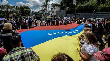 Des Vénézueliens brandissent un immense drapeau national lors des funérailles de l'opposant Fernando Alban, le 10 octobre 2018