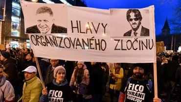 """Des manifestants brandissent une banderole avec des portraits du Premier ministre Robert Fico (D) et du ministre de l'Intérieur Robert Kalinak et le slogan """"chefs du crime organisé"""", pendant une manifestation à Bratislava, le 9 mars 2018"""