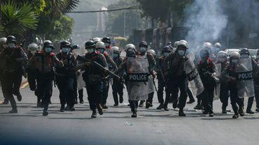 Des policiers courent vers des manifestants rassemblés contre le coup d'Etat militaire, le 27 février 2021 à Rangoun, en Birmanie