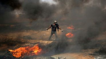 Un manifestant palestinien tire un pneu en feu durant les heurs frontaliers avec l'armée israélienne, le 11 mai 2018 dans la bande de Gaza