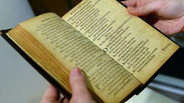 """Un employé de Sotheby tient une copie du """"Bay Psalm Book"""", datant de 1640, le premier livre imprimé sur ce qui allait devenir le territoire américain"""