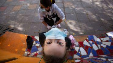 Mère aide sa fillette masquée à mettre ses rollers à Santa Cruz de Tenerife ce 26 avril 2020 (illustration)