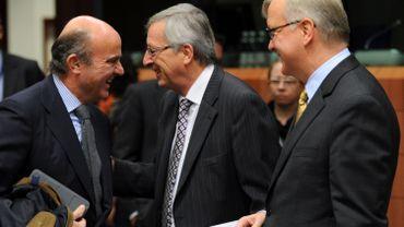 Le ministre espagnol des finances Luis de Guindos Jurados (g) en conversation avec le premier ministre et président de l'Eurogroup Jean-Claude Juncker (c) et avec le commissaire européen pour les Affaires économiques et monétaires Olli Rehn (d) ava,t une réunion de l'Eurozone consacrée à la Grèce le 20 novembre dernier.