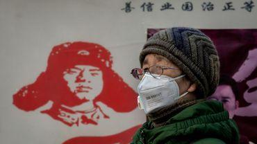 Une femme porte un masque de protection contre l'épidémie de coronavirus, près de la gare de Pékin, le 27 janvier 2020