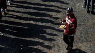Des migrants centraméricains font la queue pour recevoir un repas dans leur nouveau refuge, le 2 décembre 2018 à Tijuana (Mexique)