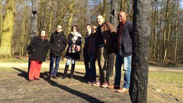 Sept élus d'Uccle et d'Ixelles posent entre les poteaux calcinés d'un ancien pavillon, pour dénoncer l'état du parc du Bois de la Cambre